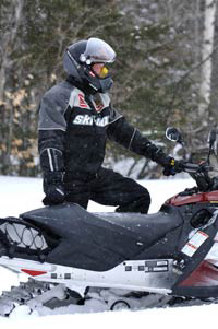 A man riding his snowmobile