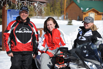 A famiy snowmobiling together