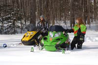 A woman rding her snowmobile