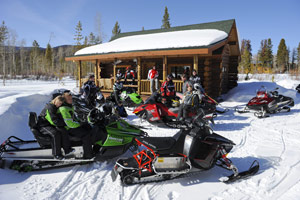 A group of snowmobilers taking a break from their sleds