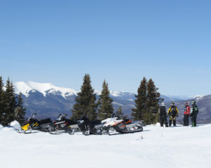 Beautiful snowmobiling scene of a group of snowmobilers and a mountain vista