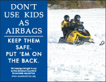 Horizontal Poster of Snowmobilers and text 'Don't Use Kids as Airbags. Keep Them Safe-Put Them on the Back'
